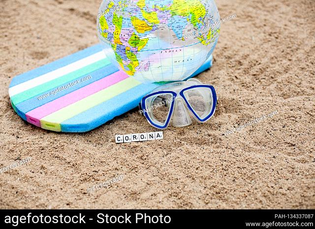 Bamberg, Germany July 28, 2020: Symbols - Coronavirus - 07/28/2020 On the sandy beach on vacation is a lettering Corona with diving mask