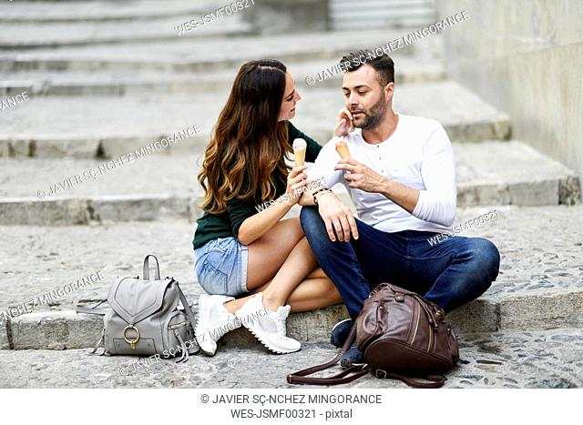 Tourist couple eating ice cream cones in the city