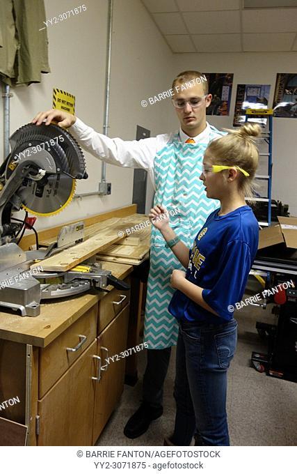 Teacher Assisting 8th Grade Girl with Circular Saw, Wellsville, New York, USA