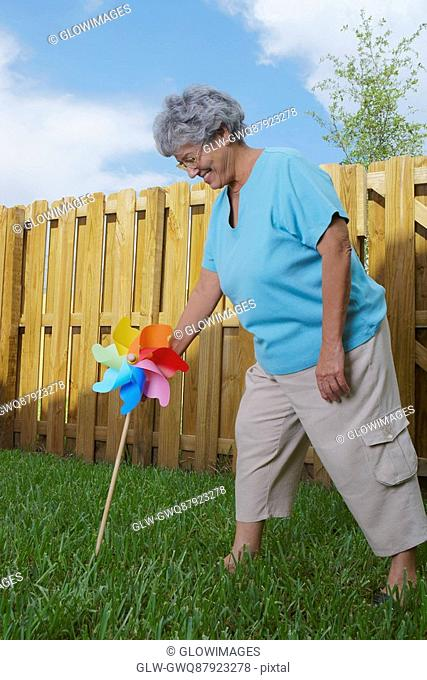 Side profile of a senior woman fixing a pinwheel in a lawn and smiling