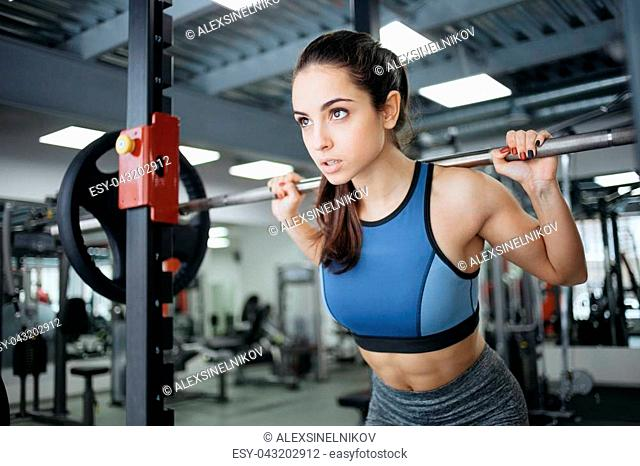 Young woman at the gym using fitness equipment. Sporty girl in blue top raising the bar and looking somewhere in front of her