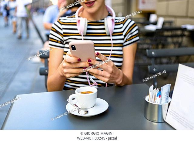 Young woman using smartphone at pavement cafe, partial view