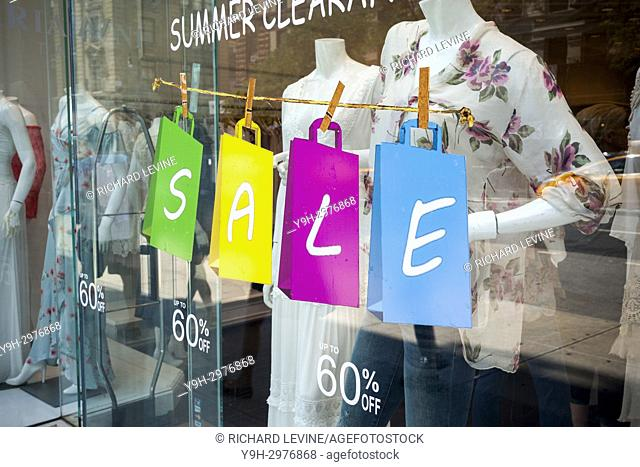 A window display in a women's apparel store in New York promotes their summer clearance sale on Sunday, July 16, 2017. (© Richard B. Levine)