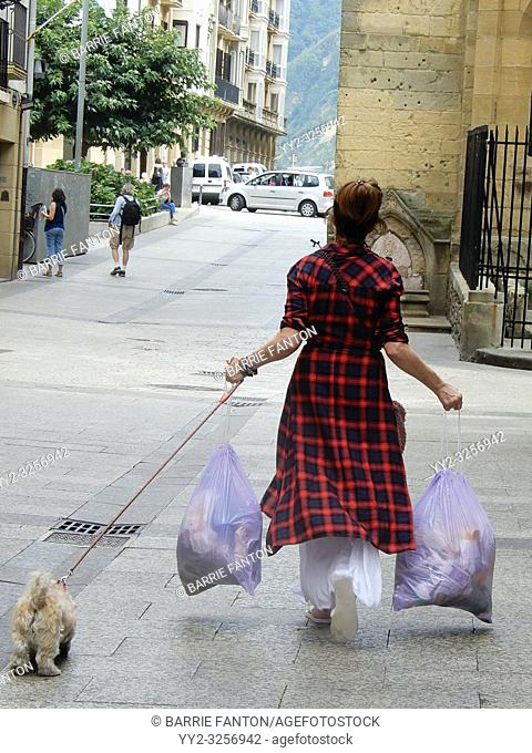 Woman Walking Dog and Carrying Trash Bags, San Sebastián, Spain