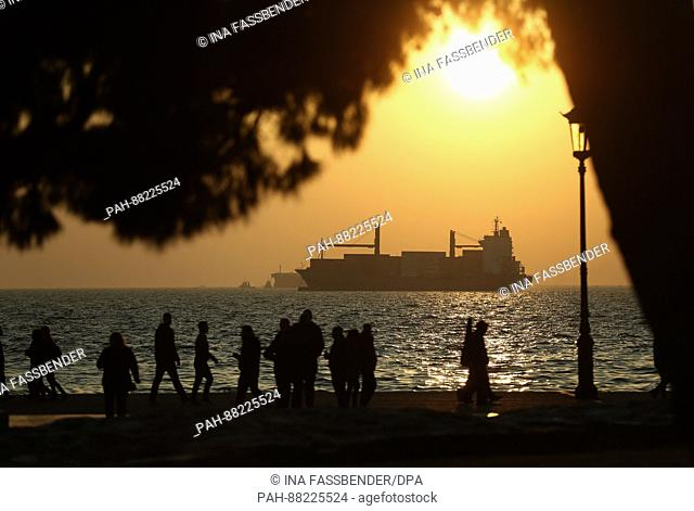 People walk along the seafront promenade, with a freighter seen in the background, in Thessaloniki, Greece, 16 February 2017