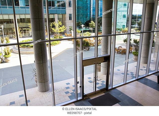 Attractive courtyard patio area as seen through the glass entrance to a modern office building complex in Silicon Valley. San Mateo, California, USA
