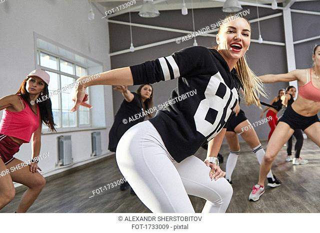 Happy young woman dancing with friends at studio