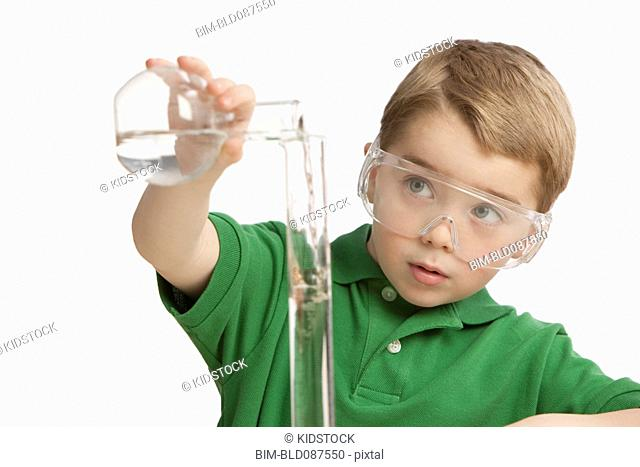 Caucasian boy putting liquid into beaker