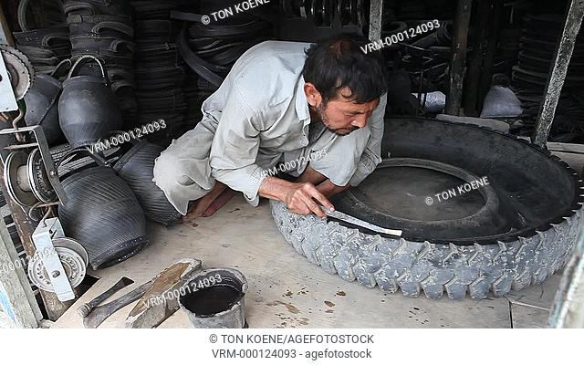 afghan man making a bucket and shoes from old car tyres