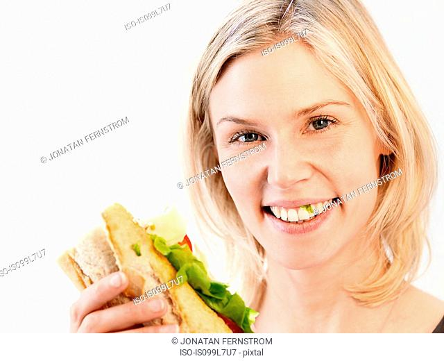 Woman smiling with lettuce caught in teeth, studio shot