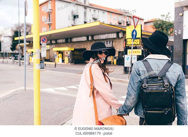 Young couple outdoors, crossing road, holding hands, laughing, rear view