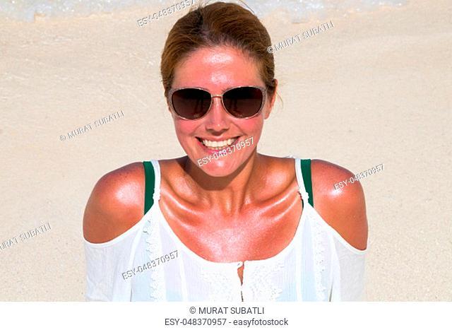 Beautiful woman in sunglasses tans at the dream beach