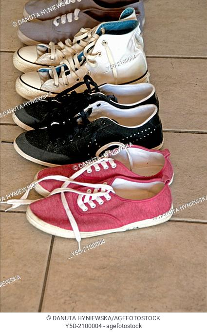 Four pairs of sneakers in a row on the floor