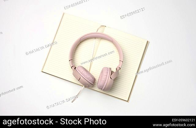 beige wireless headphones and a open notepad on a white background. Top view