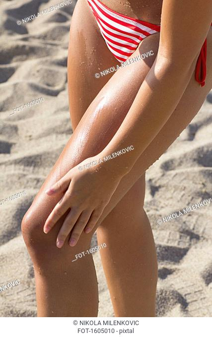 Low section of woman wearing bikini standing on beach