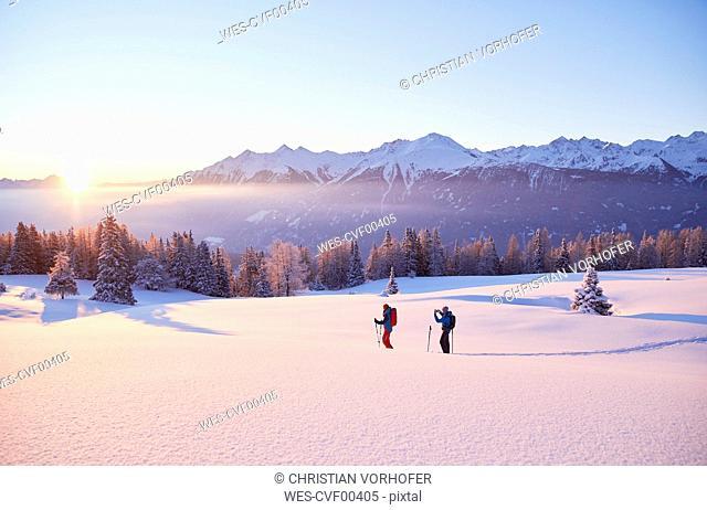 Austria, Tyrol, couple snowshoeing at sunrise