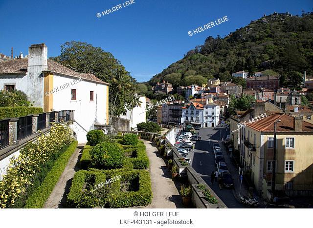 Gardens of Palacio Nacional de Sintra (Sintra National Palace) with view of old town and Castelo Mouros (Moorish castle) on hillside, Sintra, Estremadura