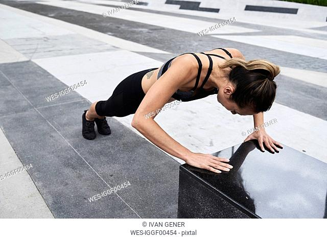 Fit woman doing push ups outdoors