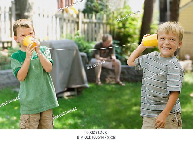 Caucasian boys using tin can phone