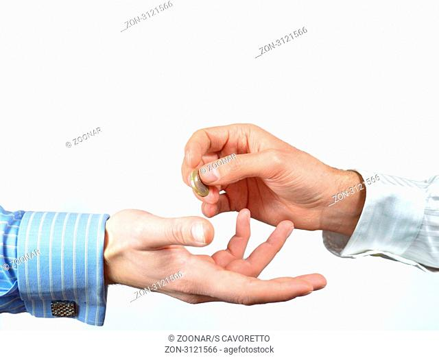 Hands exchanging one euro coin for payment or donation