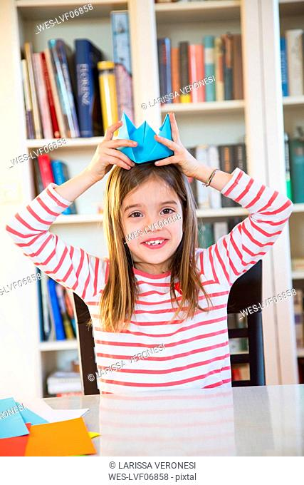 Portrait of smiling girl putting on selfmade paper hat at home