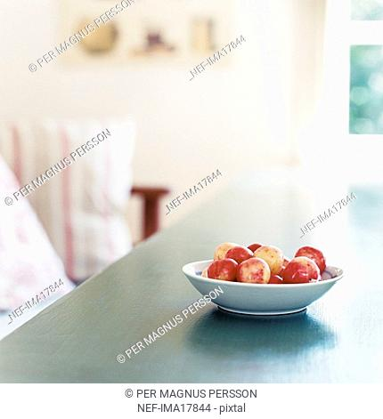Bowl with plums on table