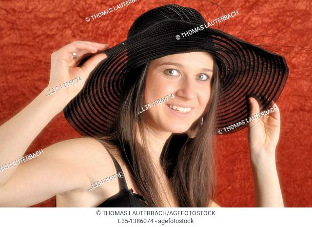Young woman playing with old, transparent, hat