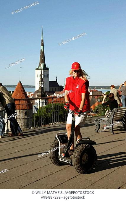 Girl riding segway in front of Lower Town City Wall Towers and St Olav Church, Unesco World Heritage, Old Town of The 13th Century Tallinn, Republic of Estonia