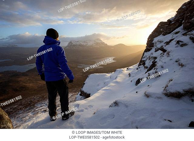 A hiker watches the sunrise from the top of Stac Pollaidh