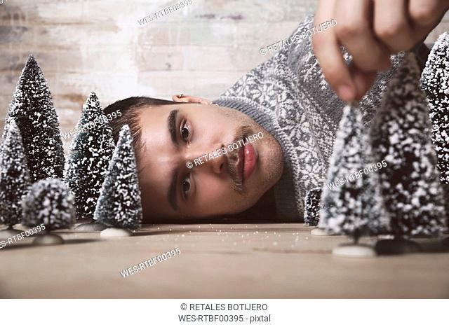 Young man lying on the floor with Christmas tree decoration