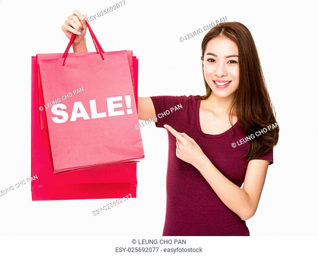Woman finger point to shopping bag and showing a word sale!