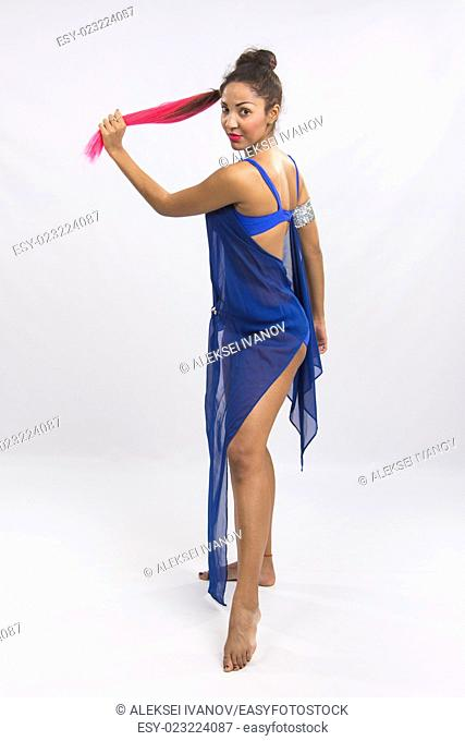 Beautiful mulatto dancer performs a dance elements, isolated on a light background