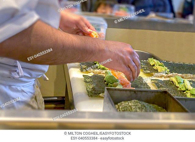 A sushi chef preparing Uramaki with avocado and salmon