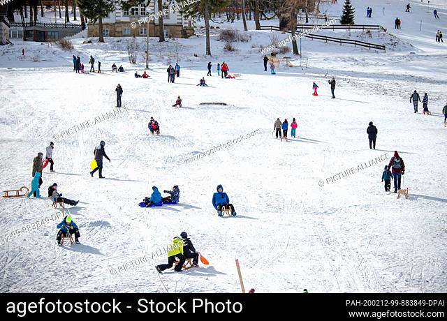12 February 2020, Saxony, Altenberg: Holidaymakers toboggan on the ski slope in partly sunny weather. A thin layer of snow attracts holidaymakers to the higher...