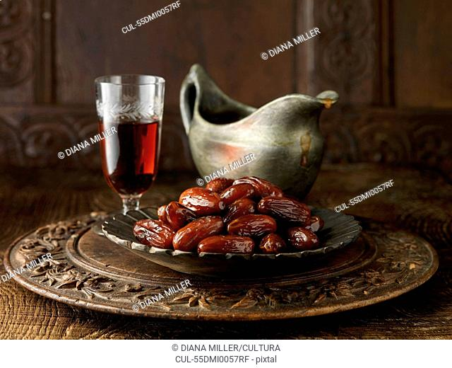 Speciality gravy containing dates and sherry on carved circular board with gray jug and crackers
