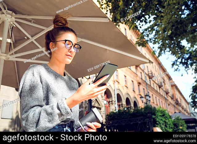 Young stylish pretty woman with smartphone at the outdoor cafe