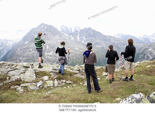 Five hikers enjoying the view on mountain peak, Austria