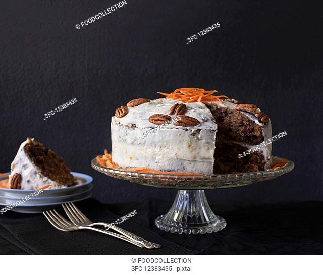 Carrot cake with pecan nuts and a piece missing on a cake stand