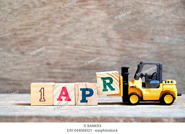 Toy forklift hold block R to complete word 1 apr on wood background (Concept for calendar date in month april)