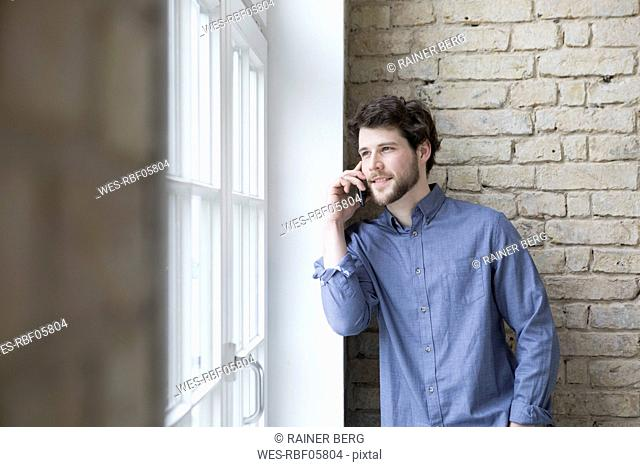 Young businessman standing at window, using smartphone