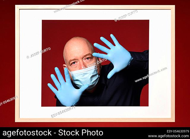 picture of man with gloves and mask with open hands on a red background