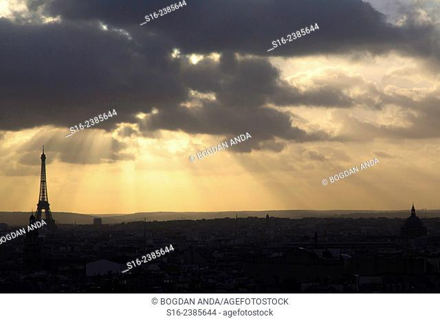 Paris, France - city skyline dominated by Eiffel Tower seen from a Montmartre rooftop, with a gloomy winter sunset sky as background