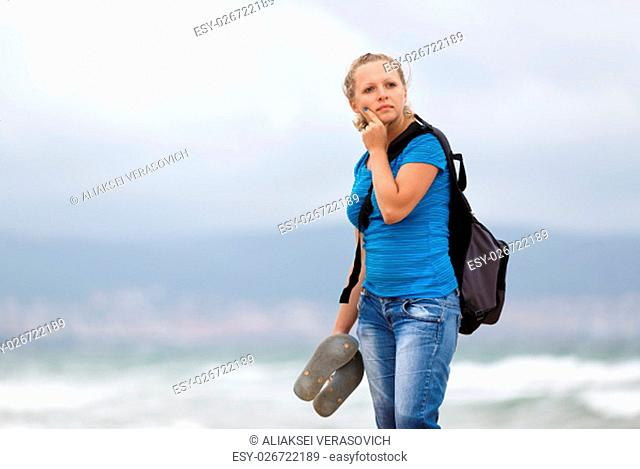Pretty young blonde woman in a blue t-shirt and jeans with a backpack standing on a sea background. Shallow depth of field. Focus on model