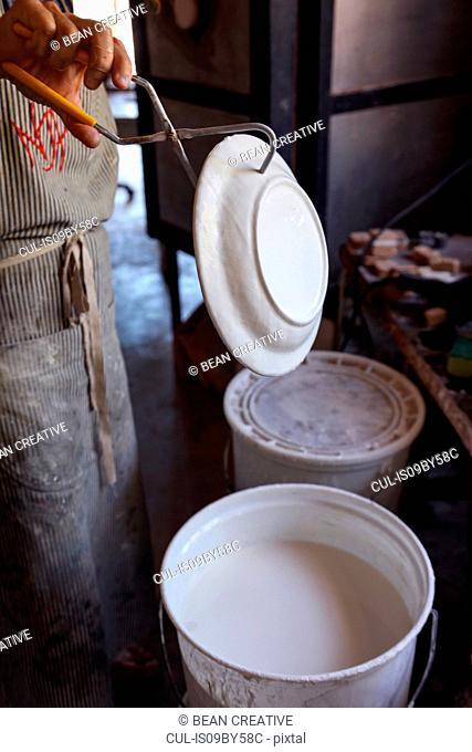 Female potter glazing ceramic in workshop