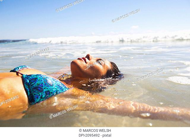 A young woman lays in the shallow water off the beach, gold coast queensland australia