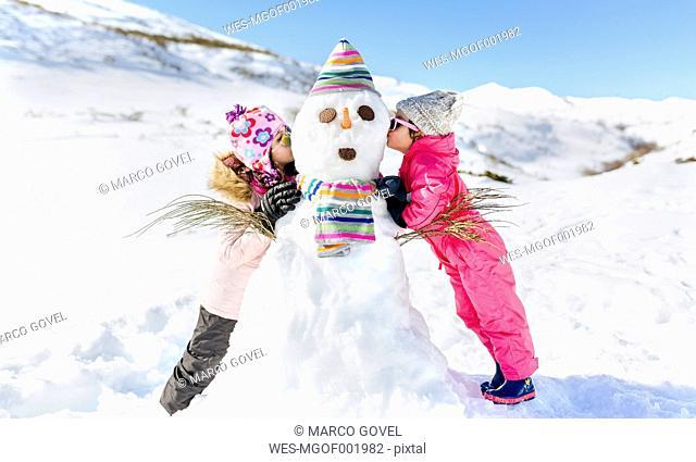Spain, Asturias, kids playing with snowmen, kissing