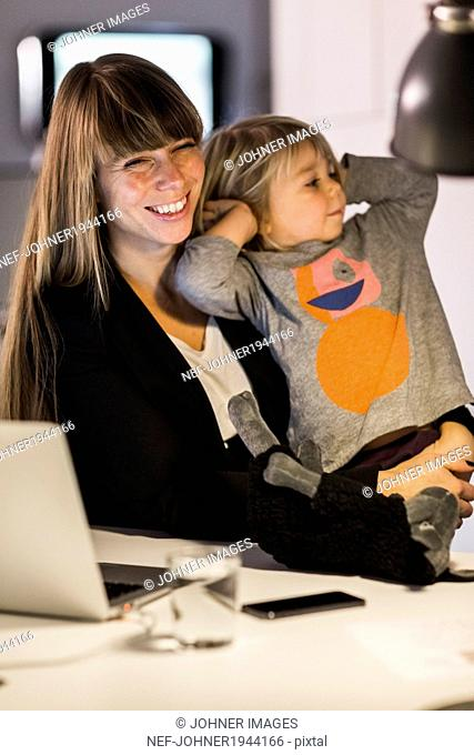 Smiling young woman in office with daughter, Stockholm, Sweden