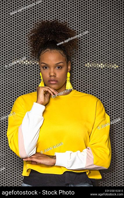 Serious black curly haired millennial female in trendy bright yellow blouse and earrings touching chin and looking at camera against mesh wall