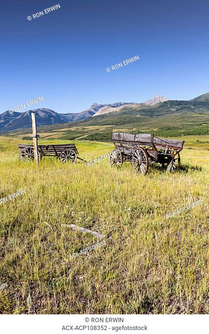 Old wooden wagons on prairie with a Canadian Rocky Mountain backdrop in Alberta