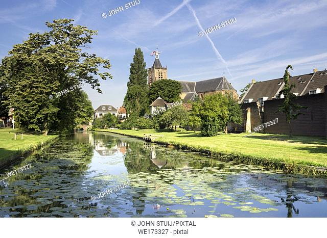 The town wall and moat from the Dutch city Vianen with the church tower in the background